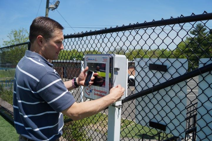 DCP employee checks AED equipment at municipal field